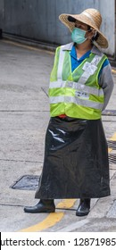 Hong Kong, China  - May 12, 2010: Female traffic warden at parking exit with fluorescent yellow jacket and face mask.
