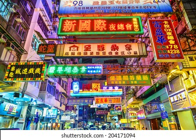 HONG KONG, CHINA - MAY 16, 2014: Signs illuminate the night in Kowloon. Hong Kong is well known for the myriad of neon lights located above the roadways.