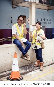 HONG KONG, CHINA - MAY 19, 2014: Two parking workers during break at workplace on May 19, 2014