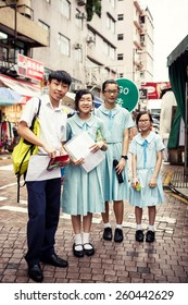 HONG KONG, CHINA - MAY 20, 2014: Group of smiling asian students standing on street of Hong Kong, China on May 20, 2014