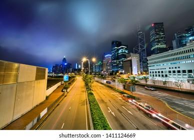 HONG KONG, CHINA - MAY 2014: City skyscrapers and traffic at sunset. Hong Kong attracts 15 million visitors every year.