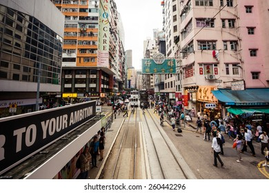 HONG KONG, CHINA - MAY 22, 2014: Group of busy people crossing the street and waiting for trams on May 22, 2014 in Hong Kong, China