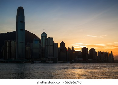 HONG KONG, CHINA - NOVEMBER 8, 2015: Silhouette of skyscrapers and other buildings on Hong Kong Island in Hong Kong, China, at sunset. Viewed from Tsim Sha Tsui, Kowloon.