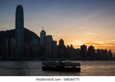 HONG KONG, CHINA - NOVEMBER 8, 2015: Silhouette of a Star Ferry, skyscrapers and other buildings on Hong Kong Island in Hong Kong, China, at sunset. Viewed from Tsim Sha Tsui, Kowloon.