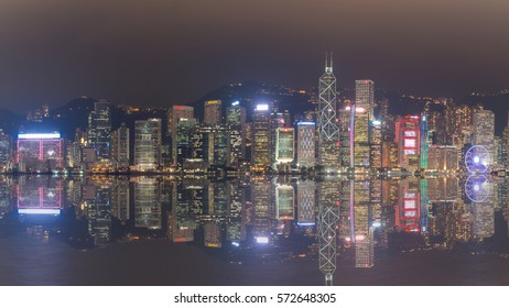 HONG KONG, CHINA - OCTOBER 12, 2016: Scenic view of Hong Kong Island's skyline over Victoria Harbor with lit urban skyscrapers in Hong Kong, China, at dusk.