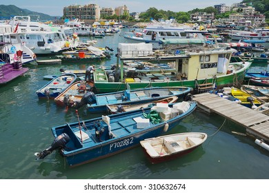 HONG KONG, CHINA - SEPTEMBER 13, 2012: Unidentified man fixes fishing boat at Sing Kee harbor in Hong Kong, China.