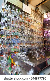 Hong Kong, China - September 23, 2016: Goldfishes and different fishes for aquarium in plastic bags hanged on the wall in a pet shop selling in Hong Kong. Customers visiting the market.