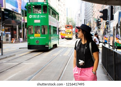 HONG KONG, CHINA - SEPTEMBER 4 : Travelers thai woman walking go to bus station at beside road with trafiic road and retro vintage tram car at Wan Chai city on September 4, 2018 in Hong Kong, China