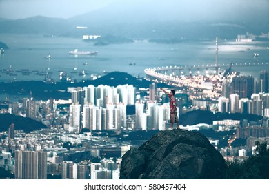 Hong Kong China,Tourist standing on the rock over a big city view from Kowloon Peak on August 1,2015