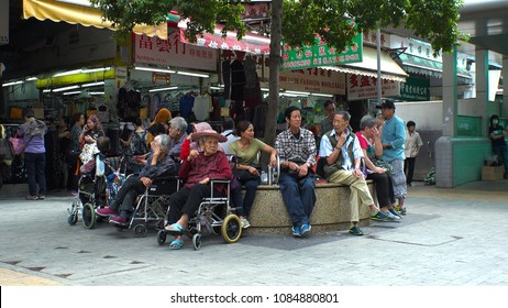 HONG KONG - CIRCA APRIL 2018 : ELDERLY PEOPLE relaxing on bench at SHAM SHUI PO area.