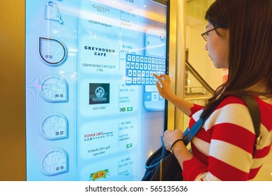 HONG KONG - CIRCA NOVEMBER, 2016: woman use interactive touchscreen at a shopping center in Hong Kong. Hong Kong shopping centers are some of the biggest and most impressive in the world
