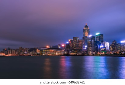 Hong Kong city skyline at night Victoria Harbor with clear sky and urban skyscrapers.