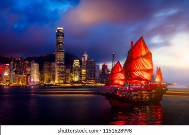 Hong Kong City skyline with tourist sailboat at night. View from across Victoria Harbor Hong Kong.