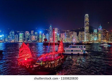Hong Kong cityscape and barque at night over Victoria Harbour.