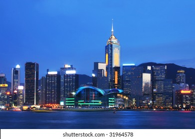 Hong Kong cityscape at night with Hong Kong Convention and Exhibition Centre located at the center of the photo.