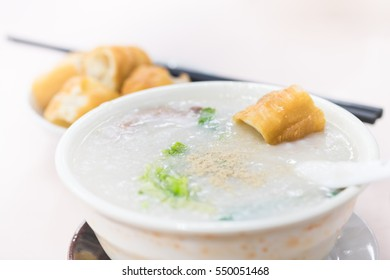 Hong Kong Congee in white bowl served with chinese doughnut