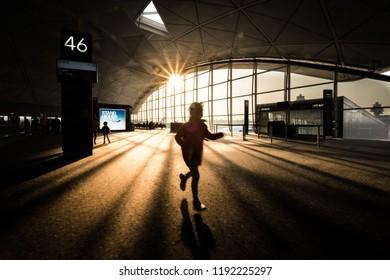 HONG KONG - DEC 2014: An unidentified girl running excitedly in Hong Kong international airport terminal building.