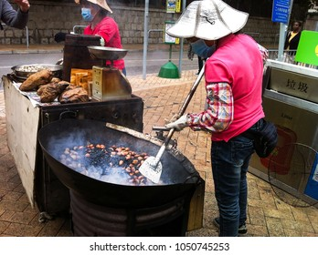 HONG KONG - DECEMBER 08, 2013: Street vendor roasting chestnuts in a large wok, popular street snack in Hong Kong