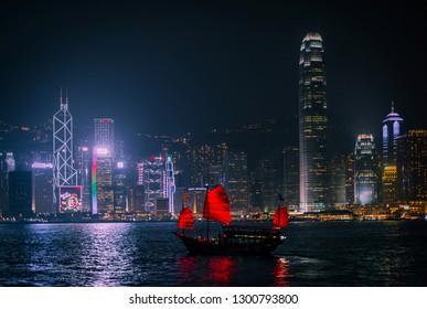 HONG KONG - DECEMBER 8, 2013: Illuminated Chinese red junk (Aqualuna) on Victoria Harbour, Hong Kong, on a foggy Winter night.