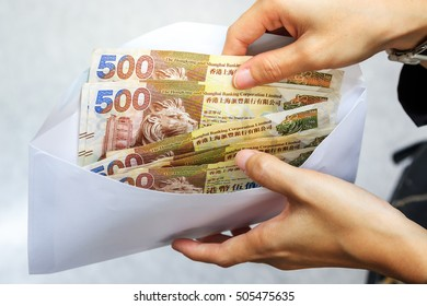 Hong Kong dollar bank notes money in white envelope and business woman hand. Hong Kong dollar bills in envelope. Female hand with money in cash with selective focus and soft focus. exchange concept