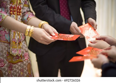 Hong Kong - February 10 2017: The Chinese groom and bride receiving red packet from parents in the traditional wedding. The red pocket represent luck and fortune.