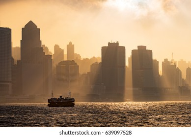 HONG KONG - February, 2017 :Silhouette of Hong Kong High rise buildings and star ferry with beautiful shaft of light. The Victoria Harbor in Hong Kong is world-famous for its dramatic panoramic view.