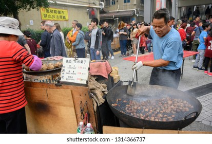 Hong Kong, February 5, 2019:A  man is seen stir-frying chestnuts with black sand in Wong Tai Sin, Hong Kong. The stir-fried chestnuts are among the popular street food in Hong Kong.