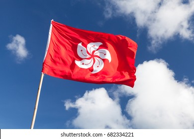 Hong Kong flag waving over blue cloudy sky background
