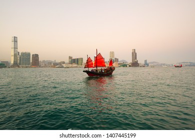 Hong kong harbour and skyline, red junk boat sailing at the foreground