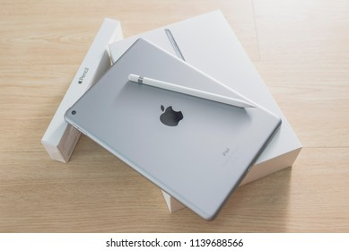 Hong Kong, Hongkong - July 22, 2018: Brand new (officially 6th gen) 9.7-inch black space grey Apple iPad and Apple Pencil with box on light colored wooden background. iPad announced on March 27, 2018.