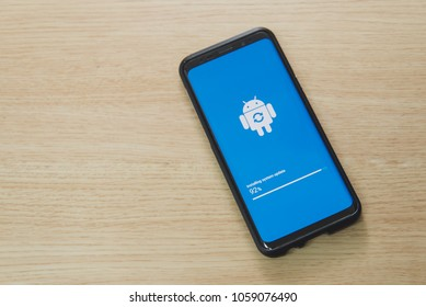 Hong Kong, Hongkong - March 28 2018: Android OS installing system update on a Samsung Galaxy S9 smartphone mobile device on a wooden background.