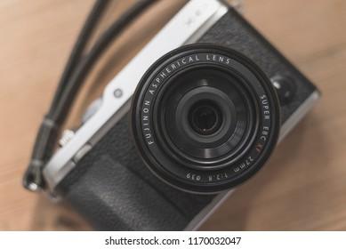 Hong Kong, Hongkong - September 3, 2018: The Fujifilm X-E3 mirrorless digital camera with Fujinon XF 27mm F2.8 prime lens on a rustic wooden surface. Shallow depth of field.
