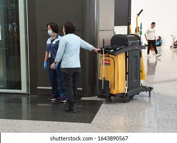HONG KONG INTERNATIONAL AIRPORT, CHINA. January 15, 2020. Two female cleaning workers wearing protection masks in the Hong Kong airport Chek Lap Kok. Novel coronavirus (nCoV), COVID-19 concept image