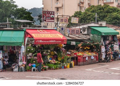 Hong Kong Island, China  - May 12, 2010: Row of market stalls sell clothing, flowers, fruits and vegetables. One booth roof sports advertisement for Mcdonalds burgers. Customers and housing in bac.k.