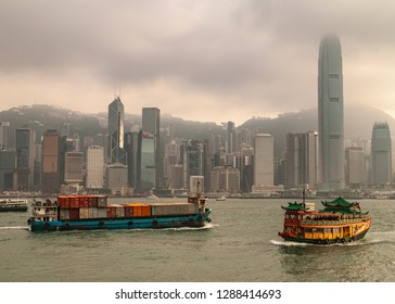 Hong Kong Island, China  - May 12, 2010: Skyline with International Finance Center and more under dark foggy sky,. Container ship and Watertours sampan-style river cruise boat on Victoria Harbour.