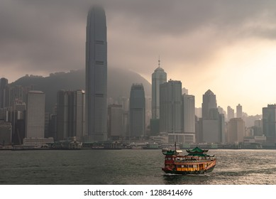 Hong Kong Island, China  - May 12, 2010: Skyline with International Finance Center and more under dark foggy sky, and one sun spot. Watertours sampan-style river cruise boat on Victoria Harbour.