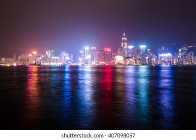 Hong Kong Island with scyscrapes illuminated by night, viewed from Kowloon, Hong Kong, China.