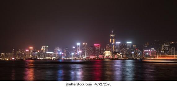 Hong Kong Island with scyscrapes illuminated by night, viewed from Kowloon, Hong Kong, China.