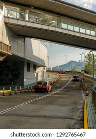 Hong Kong - Jan 20 2019: Two red taxis, and uphill road with overhead bridge at Hung Hom, Hong Kong, with Hong Kong Island skyline in the background