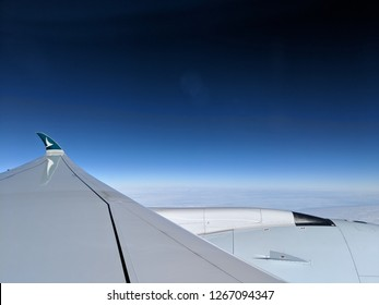 HONG KONG - JANUARY 19, 2018: Wing and engine of a Cathay Pacific flight with its new trademark logo when the plane was flying in the blue sky. Editorial Use Only.