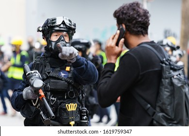 HONG KONG - JANUARY 19 2020: A riot police officer armed with a pepper spray pellet gun orders a pedestrian to move during the 'Universal Siege on Communists' rally at Chater Garden, Hong Kong.