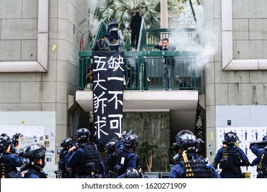 HONG KONG - JANUARY 19 2020: A man screams as riot police officers shoot at him with pepper spray pellets during the 'Universal Siege on Communists' rally at Chater Gardens, central Hong Kong.