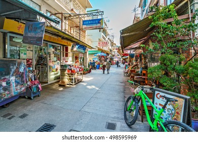 Hong Kong - January 25, 2016: Narrow but lively main street of Yung Shue Wan village on Lamma Island is lined with souvenir shops, fresh markets as well as a mixture of Eastern and Western eateries