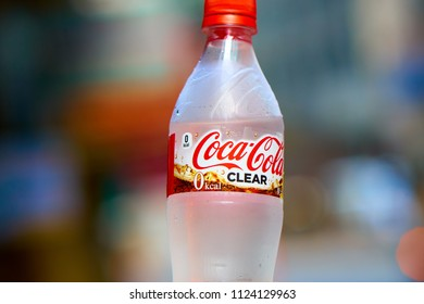 HONG KONG - JULY 01, 2018: Cold and misted plastic bottle of Coca-Cola Clear in front of defocused asian city. Illustrative Editorial.
