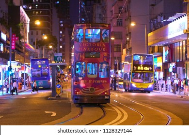 HONG KONG - JULY 03, 2018: Whitty Street tram stop for double decker trams on the street with double decker buses ride in both directions. Night time.