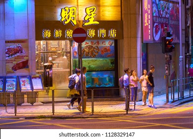 HONG KONG - JULY 03, 2018: People are waiting green light on the street corner. Seafood restaurant with big aquariums full of crabs and shellfish is on the background.