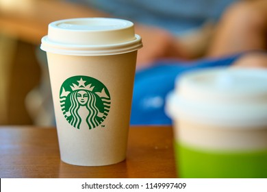 HONG KONG - JULY 1, 2018: Starbucks coffee in tall size disposable paper cup with logo on table. Illustrative editorial.