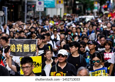 """HONG KONG - JULY 1 2019: Hong Kong people holding signage/poster of """"Investigate into Police Brutality"""" during a protest against the Extradition Bills on the 22nd Handover Anniversary Day."""