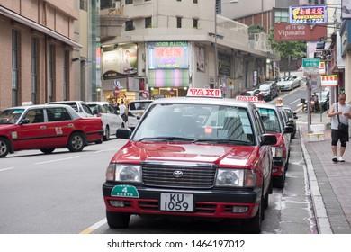 Hong Kong - July 14, 2019 : Row of Hong Kong urban red taxi cabs waiting passengers at Tsim Sha Tsui street.