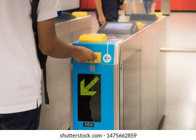 Hong Kong - July 14, 2019 : Hand holding a train ticket to subway entrance gate (Automatic Passenger Gate).